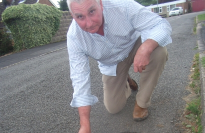 Cllr. Ian Fleetwood inspects a pothole